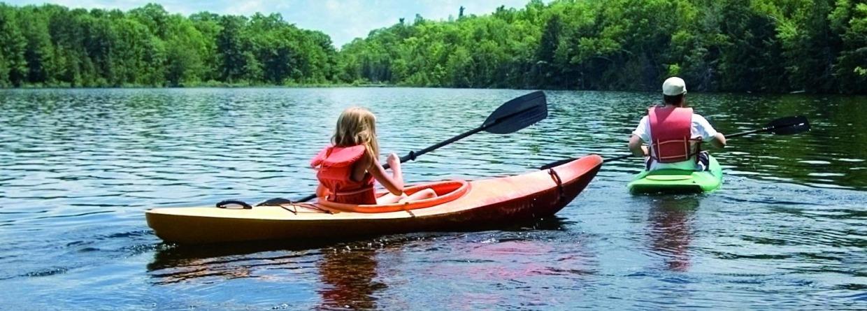 twee mensen met kano door de natuur