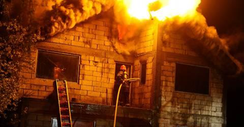 Brandweer blust een huis wat in brand staat