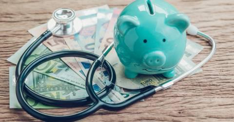 stethoscoop en spaarvarken op briefgeld